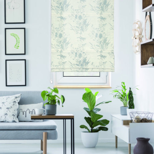 Gallery with plant posters hanging on wall in real photo of bright living room interior with window with wooden blinds and grey sofa with cushions and blanket